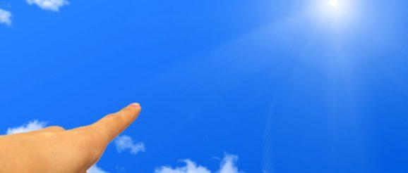 青空の太陽を指差す